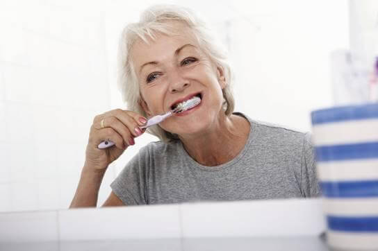Middle-aged woman brushing her teeth